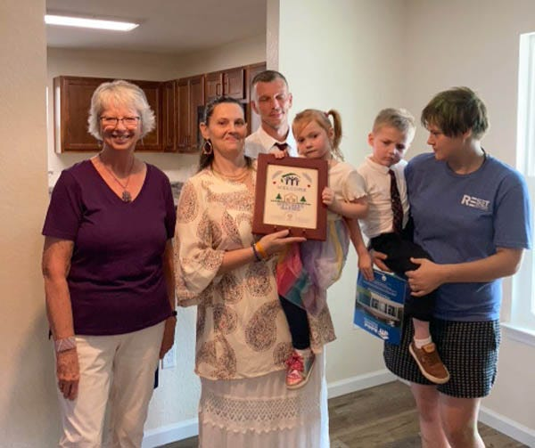 On July 16, Barbara Harrison, left, Outreach Chair for the Sand Dunes Chapter of the Embroiderers' Guild of America (EGA), presents a stitched welcome sampler to new homeowners Solitair Hutchins, Matthew Bakies and David Hutchins during their Habitat for Humanity home dedication July 16in Crestview.