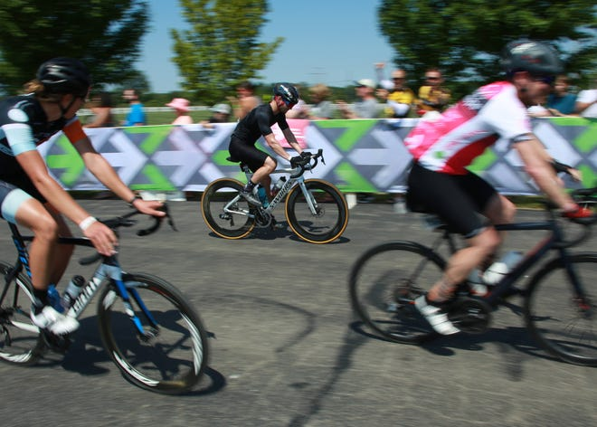 Three riders pass through the Pelotonia finish line toward the bike racks at Bevelhymer Park in New Albany in 2019. The organization announced in February that the three-day event would return Aug.6-8 after going to a virtual-only platform in 2020.