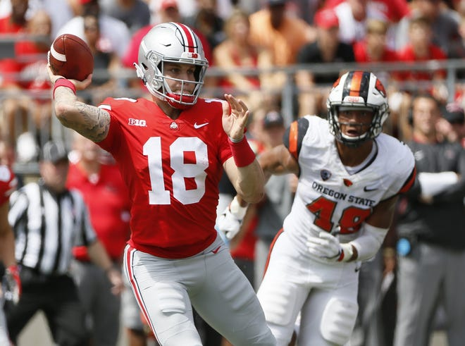 Ohio State Buckeyes quarterback Tate Martell (18) rolls out of the pocket to throw a pass in front of Oregon State Beavers linebacker Andrzej Hughes-Murray (49) during the second quarter of the NCAA football game at Ohio Stadium in Columbus on Sept. 1, 2018. [Adam Cairns / Dispatch]