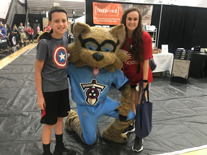Andy Barnes, 12, and aunt MacKenzie Marcrum visit with T-Rac, the Titans mascot at Experience Spring Hill.