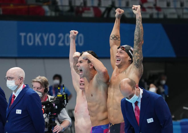 From right, Caeleb Dressel, Blake Pieroni and Bowe Becker celebrate after the United States team (including Zach Apple, in pool, not pictured) wins Sunday night's men's 4x100m freestyle relay final at the Tokyo Olympics.