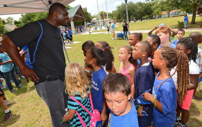 Former Fletcher High School, University of Florida and Minnesota Vikings running back Ciatrick Fason talks with kids during a 2015 literacy event.