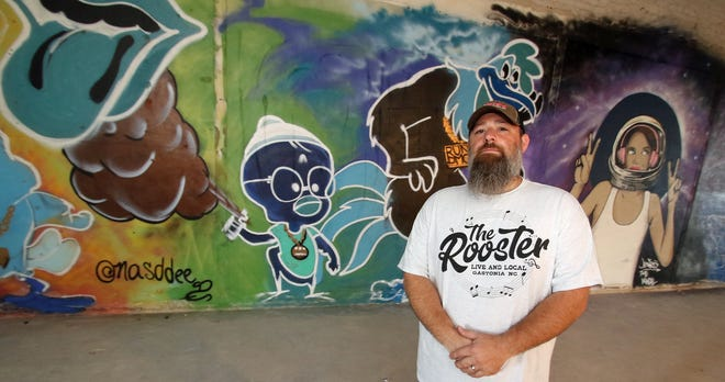Owner Michael Carpenter stands in front of the artwork of Darrell Endicott and Jason Parker on the wall inside The Rooster on West Main Avenue in Gastonia Monday morning, July 26, 2021.