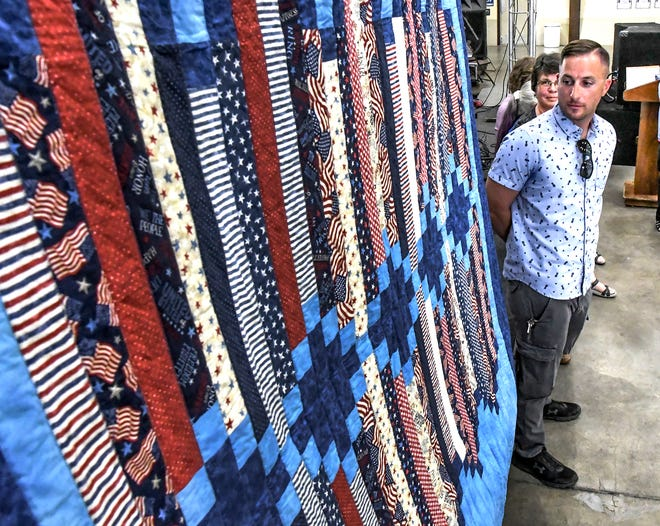 Jarrod Rosenstock checks out a quilt made for him Saturday in the Finney County fairgrounds exhibition building during a Quilts of Valor presentation. Rosenstock was among eight veterans to receive handmade quilts in honor of their military service.