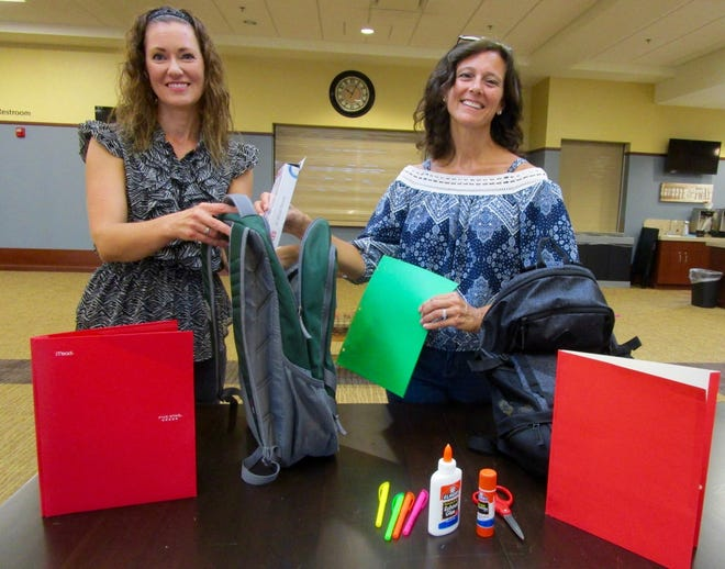 Yvette Biddle, left, director of discipleship at First United Methodist Church in Geneseo; and Andrea Masterson, a member of First United Methodist, show some of the filled backpacks that will be given to children in need in the Geneseo area.