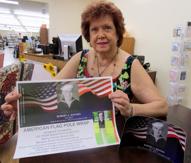 Catherine (Cat) White, owner of CIC Your Digital Print Center, LLC, in Geneseo, shows one of the American Flag Pole Wraps she created for a family to place on the flag that is part of Geneseo's Aisle of Flags display in Geneseo City Park.