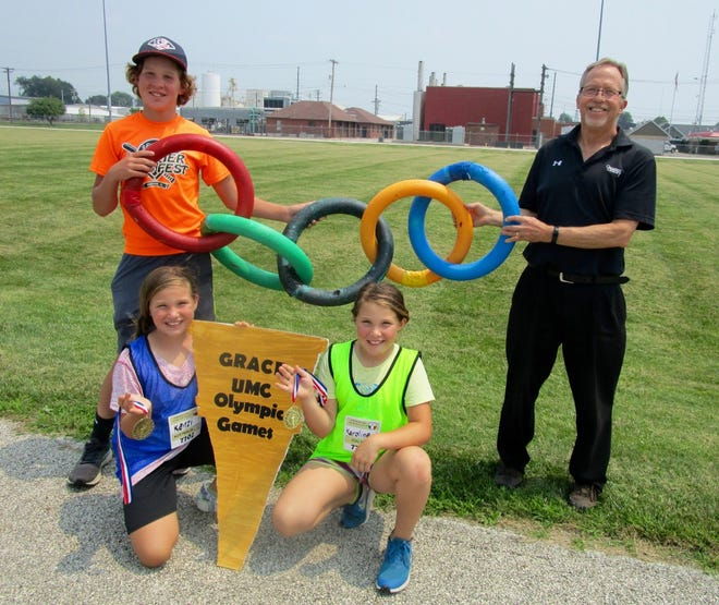 """Grace United Methodist Church in Geneseo will host a Mini-Vacation Bible School, with an Olympic theme, from 3 to 5 p.m. on Sunday, Aug. 1, at the Geneseo Park District Athletic Field on East North St. Preparing for the """"Olympics"""" are, in front from left, Kenzi Hasson and her twin sister, Karoline Hasson; in back, Jarett Hasson, who will be one of the helpers; and the Rev. Mark Graham, co-pastor at Grace Church."""