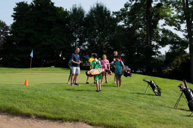 Hillsdale High School girls golf coach Nick Tucker instructs junior golfers at the week-long camp.