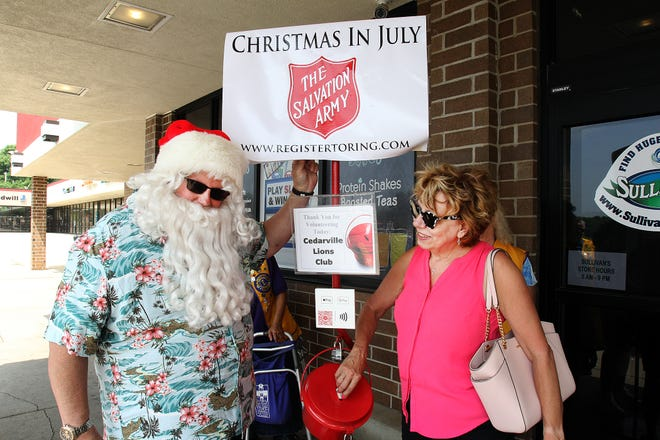 Joy Wirth, right, puts money in the red kettle as Ricky Mueller dons Santa Claus attire for the Cedarville Lions for Christmas in July for the Salvation Army on Saturday, July 24, 2021, at Sullivan's in Freeport.
