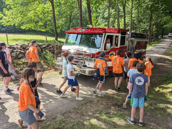 A group of teens assembled from congregations of the Church of Jesus Christ of Latter-day Saints gathers to pull a Princeton firetruck as part of a teambuilding exercise.