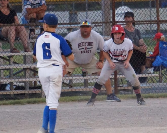 Chase Atkins gets his lead off third base for the Bedford Select 11U baseball team as he and coach John Johnson study the pitcher. The team recently won an Ohio state championship.