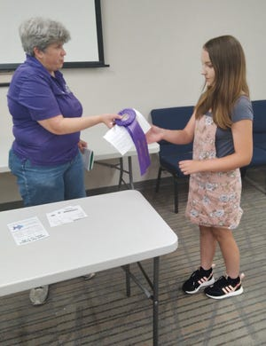 Local veterinarian and Pratt County Fair Hand Pets Superintendent Luann Bergner awards Miley O'Moore a grand champion ribbon. O'Moore also received awards for Most Knowledgeable and Most Unusual pet this year, at the fair show held in the Pratt Public Library last week.