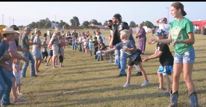 A plethora of community members line up to see who can avoid dropping a raw egg at the Kiowa County Fair Carnival Games this year.