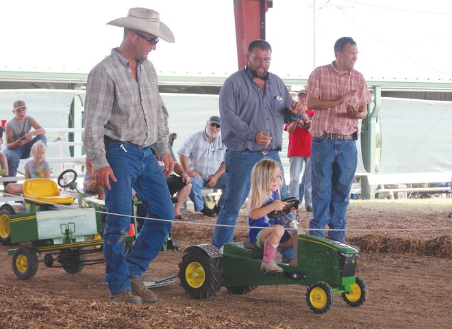 Mickey Freeman puts her pink boots to the pedals and powers through a run at the Pratt County Fair pedal tractor pull on Saturday at the fairgrounds. She, along with more than 40 other participants, were cheered on by organizers (from left) Nick Panek, Jeff Freeman, Justin Gatz and a packed house of parents and grandparents.