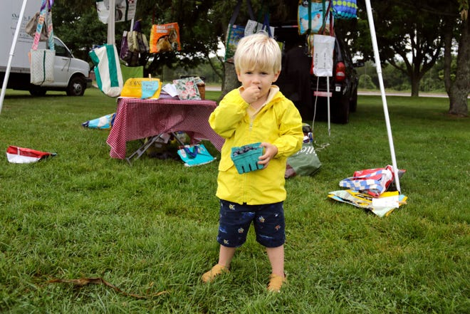 Wearing his rain jacket, Narragansett's Sawyer Sontag samples the blueberries his dad, Steve, bought Sunday at the farmers market at Fisherman's Memorial Park in Narragansett. Sunday again brought rain to the region, as the Providence area is having its third-rainiest July on record.