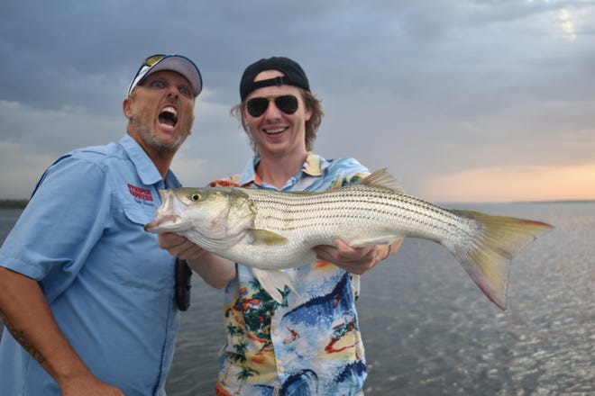 Guide Chris Carey (Lt) and Luke's grandson Luke Zimmerman having a big time showing off one of many hard fighting stripers landed earlier this week.