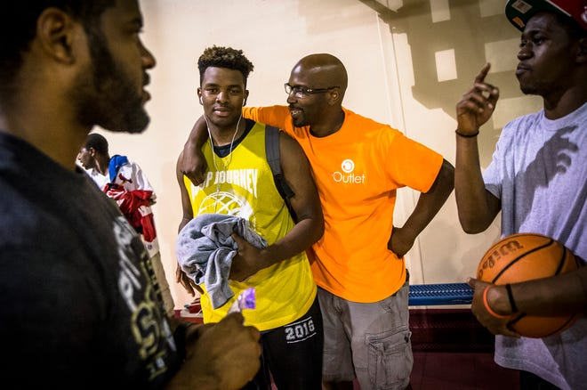 Michael Phelon, center, founder of The Outlet, talks with J.J. Lavow, a Southeast student and member of the Illinois Elite team, prior to their game starting during The Outlet's Hoop Journey summer basketball league at the Abundant Faith Christian Center, Monday, June 20, 2016, in Springfield, Ill. File/The State Journal-Register