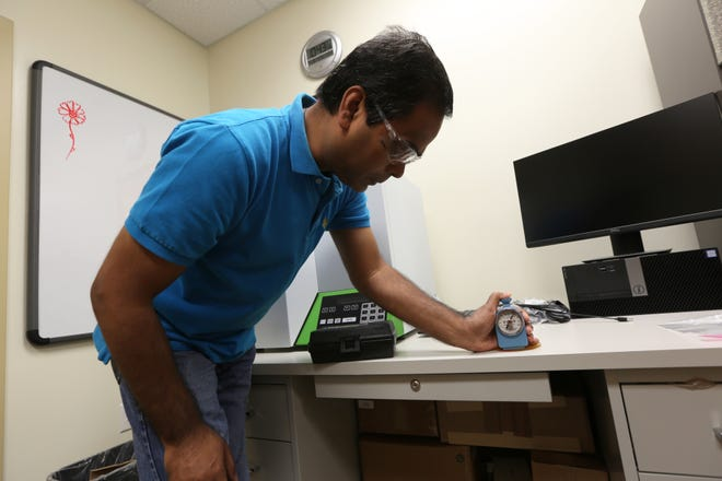 Ram Gupta testing the soybean oil based polymer he and his team have developed for eco-friendly golf balls.