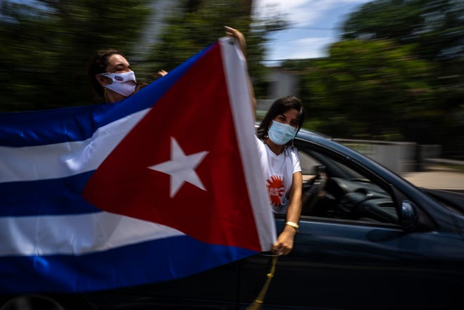 People wave a Cuban flag from a moving car during a rally to protest the U.S. embargo against the island nation in Havana on June 23, 2021. The United States voted against a U.N. resolution Wednesday that overwhelmingly condemned the American economic embargo of Cuba for the 29th year, maintaining the Trump administration's opposition and refusing to return to the Obama administration's 2016 abstention.