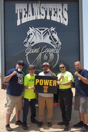 """From left to right: Anthony """"Buck"""" Buckner, Gustavo Renteria, Diego Villagomez, Adan Soto and Matt Lundy celebrate after workers at a Keurig Dr Pepper factory in Victorville narrowly voted to unionize with Teamsters Local 896."""