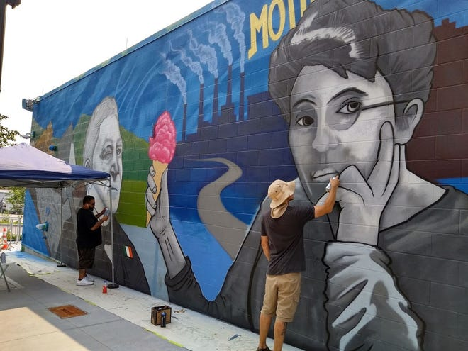 Ferdinand Nazario, left, and Ryan Gardell work on a mural on  Ash Street depicting legendary figures from the Canal District's history, including Tobias Boland, left, and Emma Goldman.