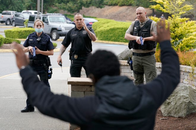 Ken Westphal, center, an officer with the Lacey Police Department and an instructor at the Washington State Criminal Justice Training Commission, works with cadets LeAnne Cone, of the Vancouver Police Department, and Kevin Burton-Crow, right, of the Thurston County Sheriff's Office, during a training exercise on July 14, 2021, in Burien. Washington state is embarking on a massive experiment in police reform.
