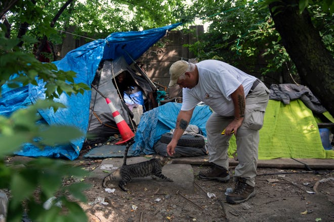 Tom Peculski, a volunteer with Helping Hands Homeless Outreach Program pets one of several cats at an encampment Monday, July 26, 2021 in Camden, N.J.