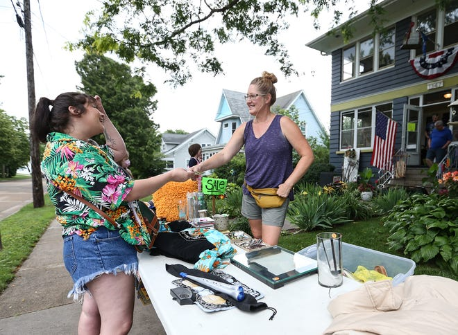 Kinni Peters of Oshkosh pays Patti DeDecker of Oshkosh for two dresses from the early' 70s Saturday at a rummage sale in Oshkosh.