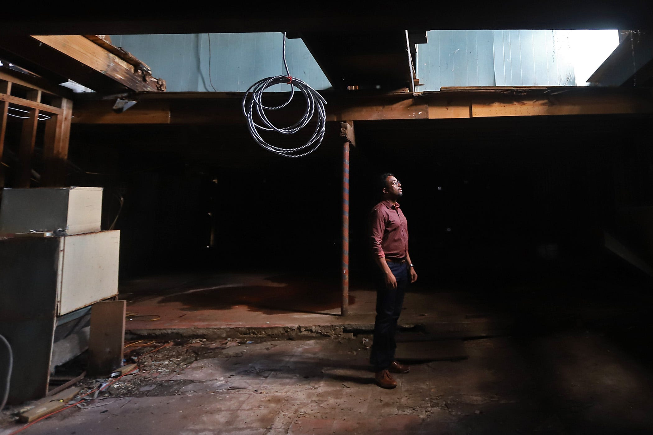 Curtis Doucette Jr. looks up at part of the ceiling that had fallen in at the historic hotel and nightclub The Dew Drop Inn in New Orleans. He plans to turn the place into a boutique hotel.