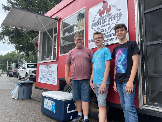Brothers Alexander (center) and Jacob Kova (right) came up with the idea for their family's new food truck, Two Brothers BBQ Mac Shack, with their father John O'Brien, shown at Pinckney's food truck rally Friday, July 23, 2021.