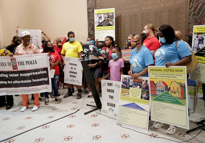 People gather as Taylor Vessel, an MATC student, speaks at City Hall in Milwaukee during a news conference fighting for affordable housing on Monday, July 26, 2021.