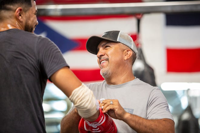 Professional boxing trainer Joel Diaz laughs with Miguel Hernandez inside Diaz' boxing gym in Indio, Calif., on July 23, 2021.