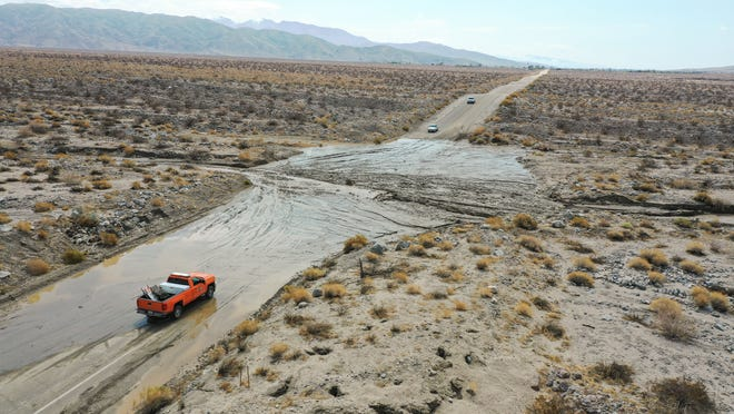 Vehicles stop on Dillon Road about a mile east of Thousand Palms Canyon Road in the Coachella Valley in California after heavy rain deposited mud and rocks there, making the road largely impassable.
