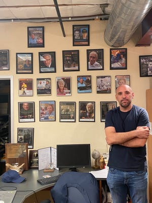 Anthony Fusco, Educational Coordinator, stands next to photos of Holocaust survivors at the Cutler-Plotkin Jewish Heritage Center in Phoenix on July 22, 2021.