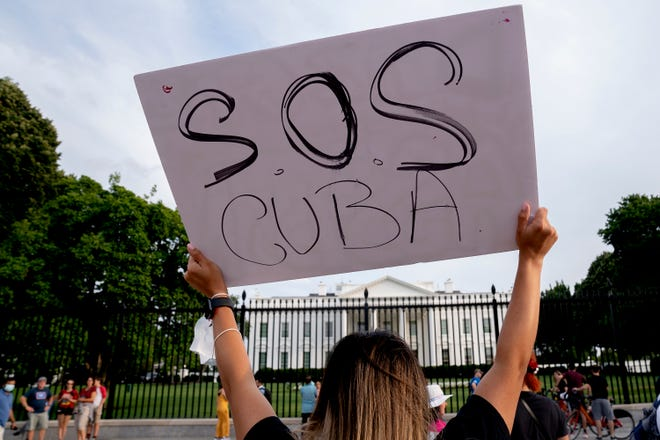 A demonstrator gathers with others in solidarity with protests in Cuba outside the White House on July 18, 2021 in Was,hington, D.C. The protests come amid demonstrations in Cuba over the lack of food, the pace of COVID-19 vaccinations and the government. (Stefani Reynolds/Getty Images/TNS)