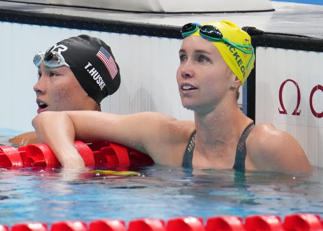 Torri Huske (USA) and Emma McKeon (AUS) look up at the results in the women's 100m butterfly final.