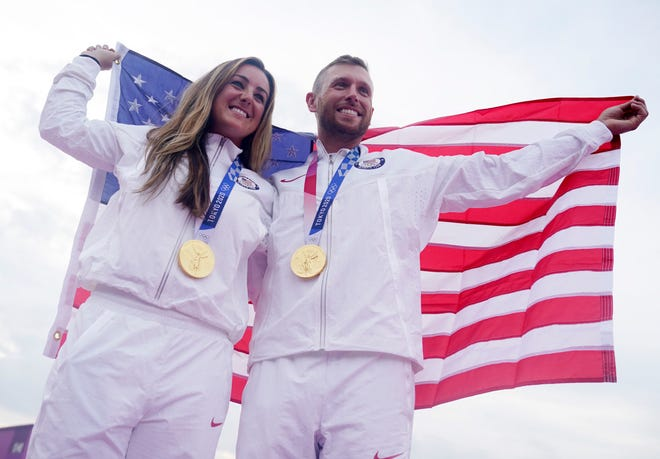 Amber English and Vincent Hancock celebrate their gold medal wins in the women's and men's skeet shooting events.