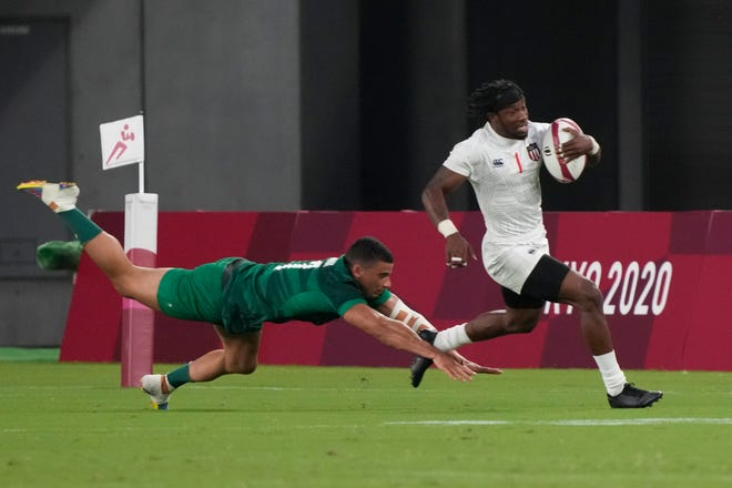 Carlin Isles of the United States evades a tackle by Ireland's Jordan Conroy in their men's rugby sevens match.