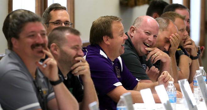 North Royalton coach Nick Ciulli, center, and Revere coach Rob Karovic, right, laugh with other Suburban League coaches during a luncheon, Tuesday, July 27, 2021, in Stow, Ohio.