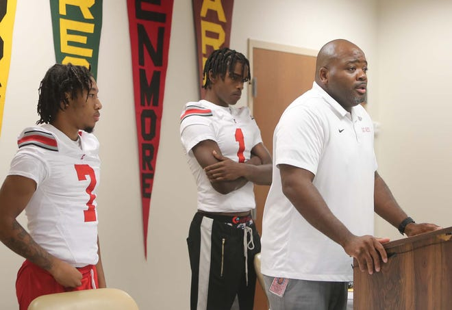 East head football coach Marques Hayes, right, speaks as he stands with seniors Navion Steadman, left, and Eric Holley III as he speaks during the Akron Public Schools Annual Football Media Day, Tuesday, July 27, 2021 in Akron, Ohio.