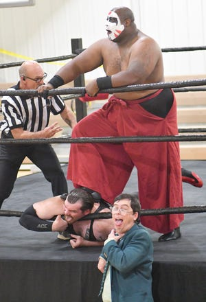 """""""The Monster"""" Tetchi Makuji uses the bottom rope to choke """"Delicious"""" Don Yoder at the Fuzion Pro Wrestling event at the Screven County Recreation Department gymnasium. While Tetchi is inflicting pain, the 360-pounder's manager, Dr. Joseph Brock III, mocks Yoder."""