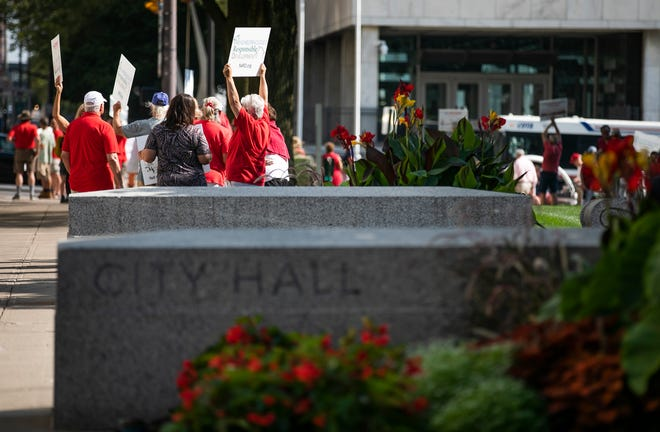 Residents protest outside Columbus City Hall on Monday against a request by The Pizzuti Companies for zoning changes needed to redevelop the site of a former Giant Eagle grocery store in Schumacher Place near German Village into a 262-unit apartment building and 8,250 square feet of retail space.