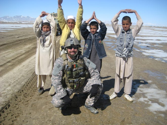 Sean Clifton, takes an O-H-I-O picture with children in the Ghazni Province of Afghanistan in February 2009. Clifton received a Purple Heart for being wounded during action as a member of the U.S. Army Special Forces, and as a member of the Dublin Veterans Committee, he worked to have Dublin recently designated as a Purple Heart City.