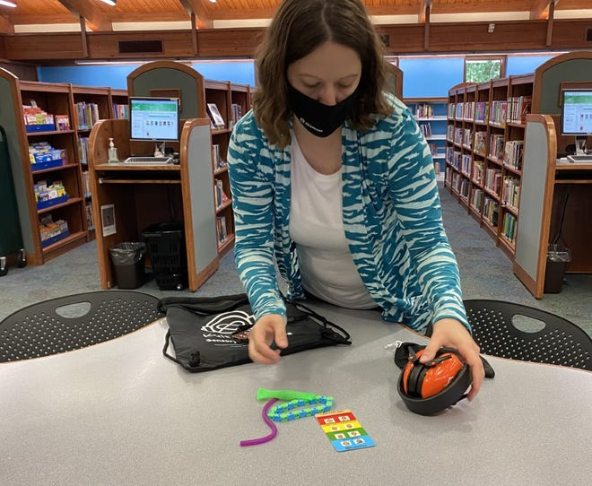 Grace Walker, a youth services librarian at the Pickerington Public Library, displays new sensory-inclusive items available at both branches to help people with autism, dementia, PTSD and other similar conditions handle sensory-overload situations.