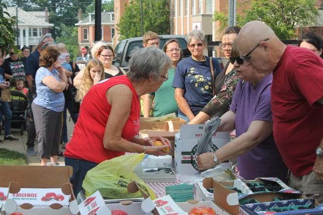Customers line up to purchase fresh produce from the Witten Farm Market at the Courtside Open Air Market of Cambridge held on the on the front lawn of the Guernsey County Courthouse.