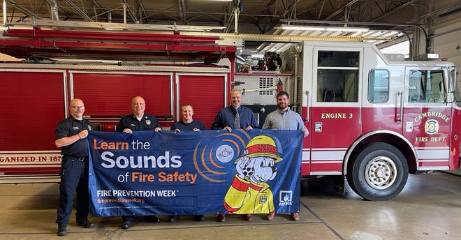 Cambridge firefighters including Chief Jeff Deeks and State Farm agents Allen Hunter and Zack Baker encourage area residents to 'Learn the Sounds of Fire Safety' during Fire Prevention Week.
