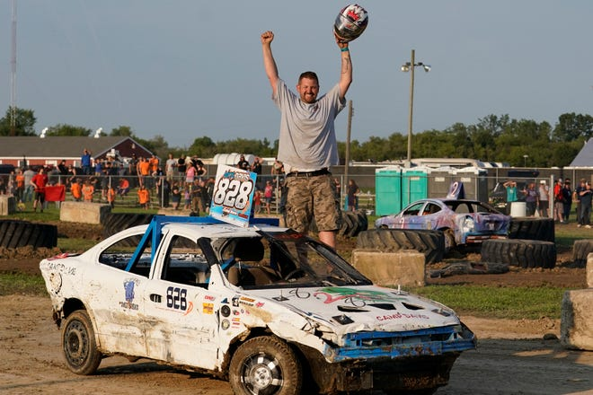 Nicholas Davis, driver of the No. 828 car in Monday's figure 8 demolition derby at the Lenawee County Fair grandstand, celebrates his first heat victory.