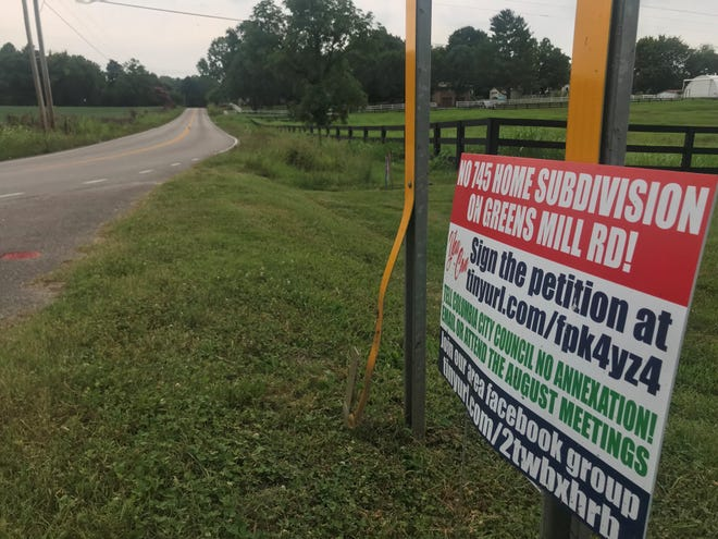 Dozens of residents on Greens Mill Road have displayed signs opposing a proposal for a 700-home residential development that they say would ruin the pastoral landscape and increase traffic.