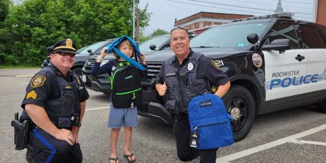 Rochester Police help distribute free backpacks donated by Guyer International Travel in a past year.