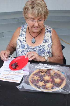 Janelle Gibson examines a bumbleberry pie while serving as a judge at the 2019 Orion Fall Festival pie contest at the bandshell in Central Park. This year's contest and auction will be Friday afternoon, Sept. 3.